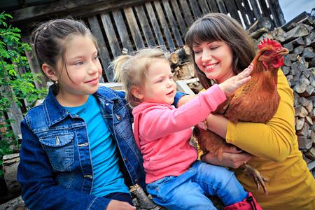 ovejitas: una familia de granjeros con una gallina delante de la finca Foto de archivo