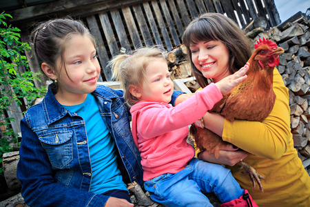 a farm family with a hen in front of the farm