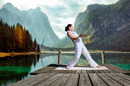 tai chi: young woman making tai chi exercise at a lake