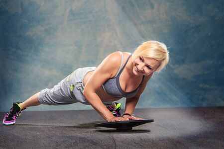 barbel: studio portrait of a young woman by doing push-ups