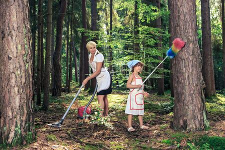 yard work: symbolic picture with mother and daughter by cleaning of the forest