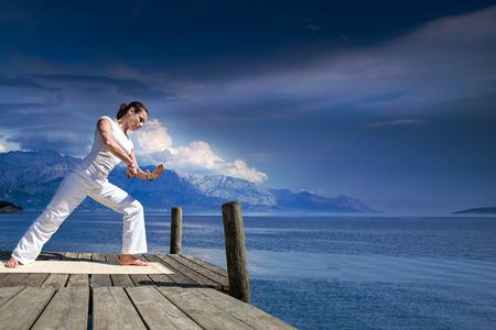 young woman making tai chi exercise at a lake