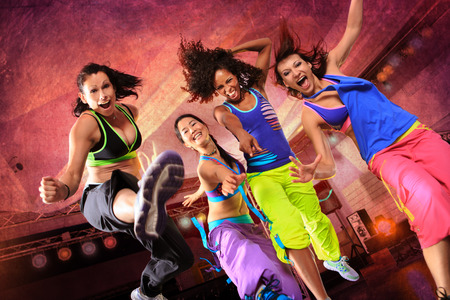 'fit body': young women in sport dress jumping at an aerobic and zumba exercise Stock Photo