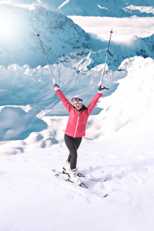 winter vacation: A young woman skiing in the mountains