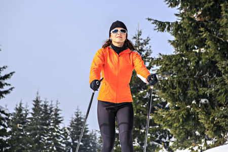crosscountry: A woman cross-country skiing in the wintry forest