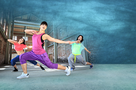 group of  women in sport dress dancing zumba or aerobics