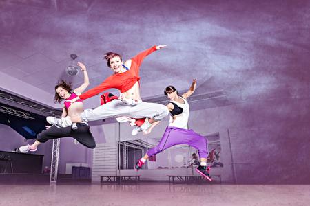 gimnasia aerobica: grupo de mujeres en traje de deporte que saltan en la aptitud ejercicio de baile o aeróbic