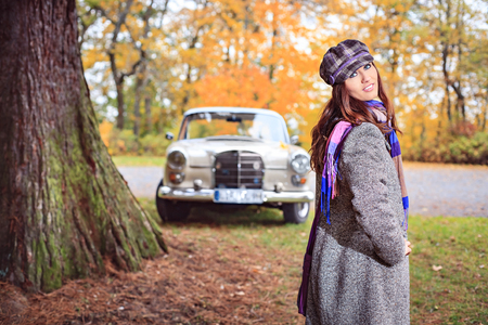 postwar: A young woman in front of Post-War classic car