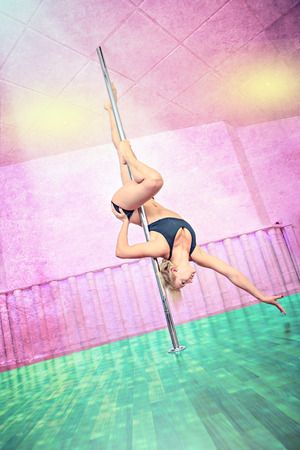 pole dancing: a women in sport dress pole dancing at the fitness studio