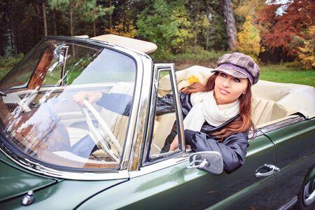 postwar: A young woman in front of Post-War classic car