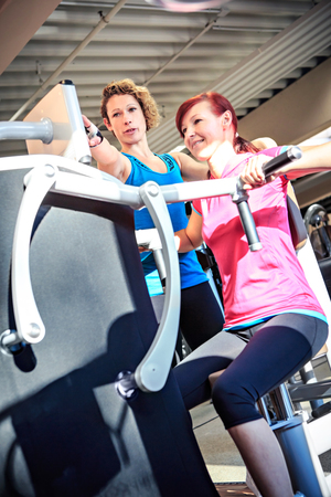 barbel: young woman on a fitness machine in a gym