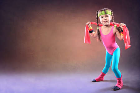 Little  girl with a rubber strap at fitness exercise photo