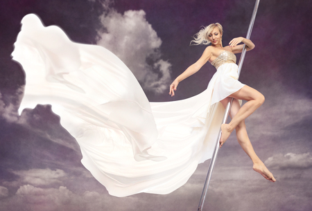 pole dancing: a women in a dress pole dancing in front of sky