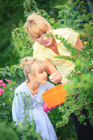 togheter: young girl and her mother working in the garden