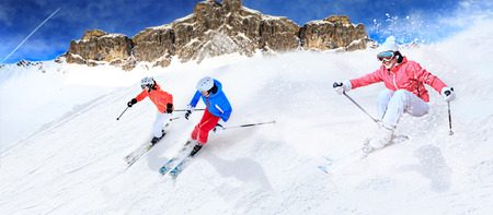 Dynamic picture of three ski driver on the piste in Alps photo