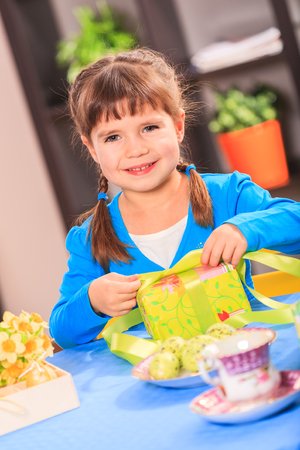 a young girl packaging gift  for eastern photo