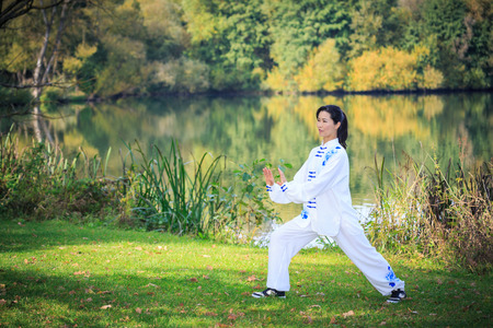 young woman doing a taichi or qi gong exercise at a lake Banco de Imagens - 83344313
