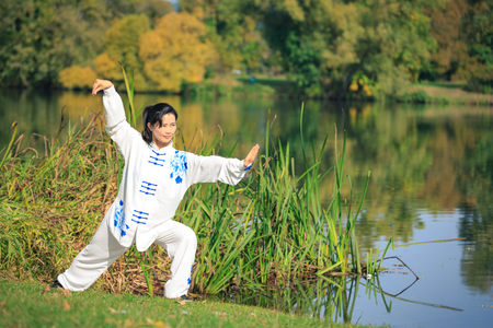 Young woman doing a taichi or qi gong exercise at a lake 스톡 콘텐츠