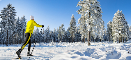 A woman cross-country skiing in the wintry forest
