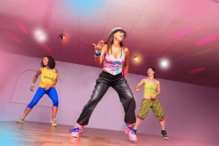 Junge Frauen im Sport ziehen sich bei einer Aerobic- oder Zumba-Übung an