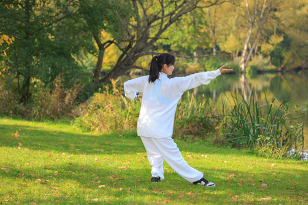 young woman doing a taichi or qi gong exercise at a lake Stock Photo
