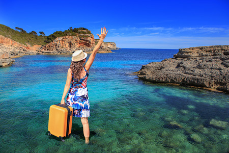 Portrait of a young woman with a suitcase on the beach Stock Photo