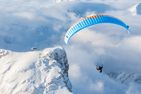 The paraglider in the air over the wintry mountains