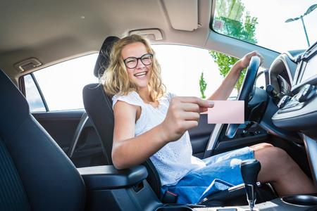 ein junges Mädchen nach erfolgreicher Fahrprüfung in einem neuen Auto