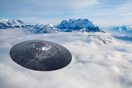 An UFO on approach over clouds and mountain area Stock Photo