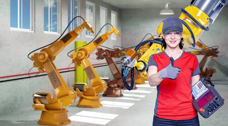 A young female technician while machine constructing in a manufacturing plant Reklamní fotografie