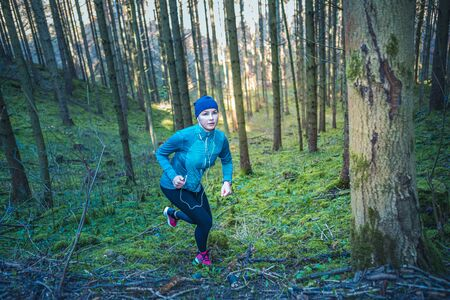 young girl jogging in the forest at spring time