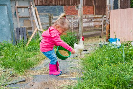 little girl feeding chickens in front of farm
