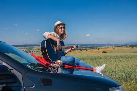 a young girl plaving guitar on the bonnet of her car on the countryside journey Imagens