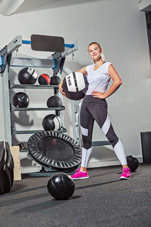 young girl working out with ropes at the gym or in the fitness room Imagens