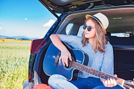 a young girl plaving guitar in the car on the countryside journey Imagens