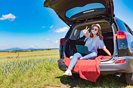 a young girl with the laptop in a car on the countryside journey Imagens