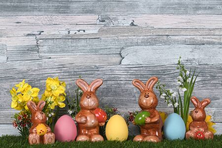 Four Easter bunnies with the colored eggs
