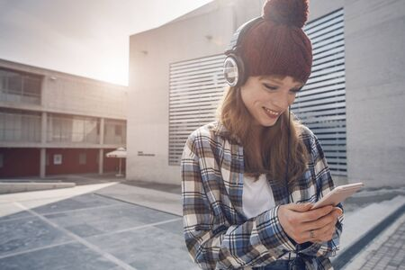 sms: a young woman wearting a beanie and headphones, that is using a music application in her smart phone device while in an urban, modern city architecture environment Stock Photo