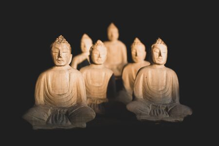 Meditating wooden buddha statues sitted in lotus