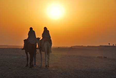 two camels riding towards the sun in the desert Stock Photo