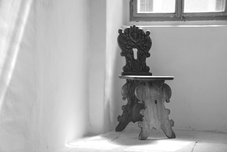 an old chair is made of wood in the corner in a castle photo
