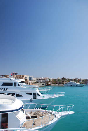 many white boats on the harbor with turquoise blue sea egypt