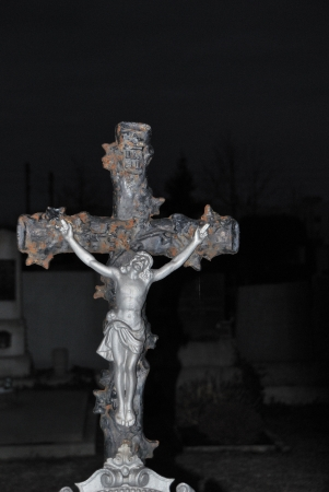cemetery cross with Jesus on an image in the night photo