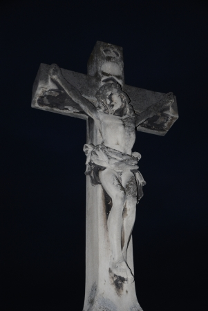 cross with jesus image on a large cemetery in view of the night photo