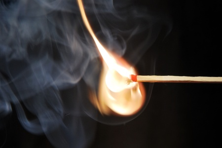 ignited: match ignited with a beautiful orange flame with black background Stock Photo