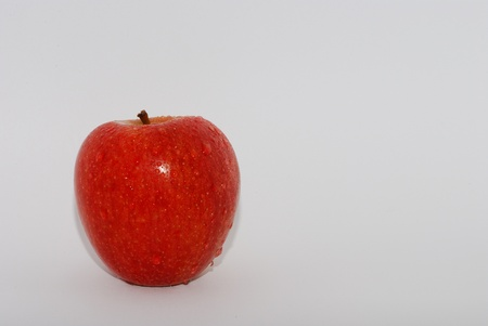 fresh sweet red apple with water drops on white background left photo