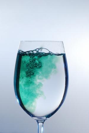 green bubbling liquid in a wine glass photo