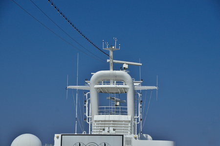 top of white ship with antennas and blue sky