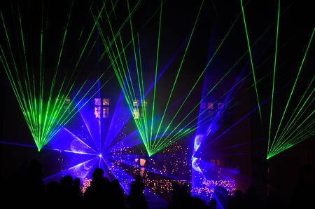 laser show with blue green glow in the night