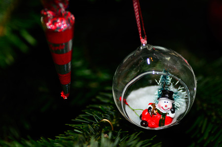 small snowman in ball on a christmas tree photo